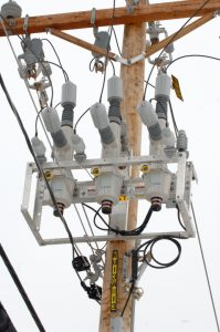 An electrical device on power lines and poles.